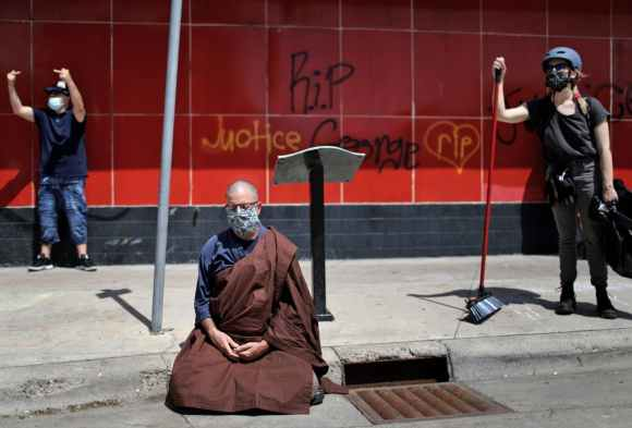 Ben Connelly, a Buddhist priest at the Minnesota Zen Meditation Center, prayed while seated near E. Lake Street and across from the Minneapolis Police's Third Precinct station.