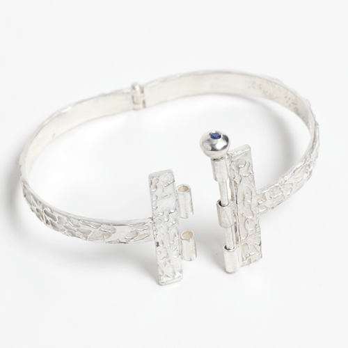 Sudina bracelet, hinged based with a pin claps closure and flush set blue sapphire