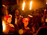 women dance with flame atop stems of metal