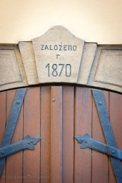Wooden doors with iron hinges and 1870 engraved above it.