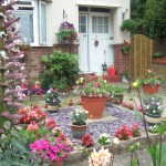 Colourful front garden with plants in pots and beds