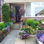 Colourful front garden with plants in beds and free-standing containers