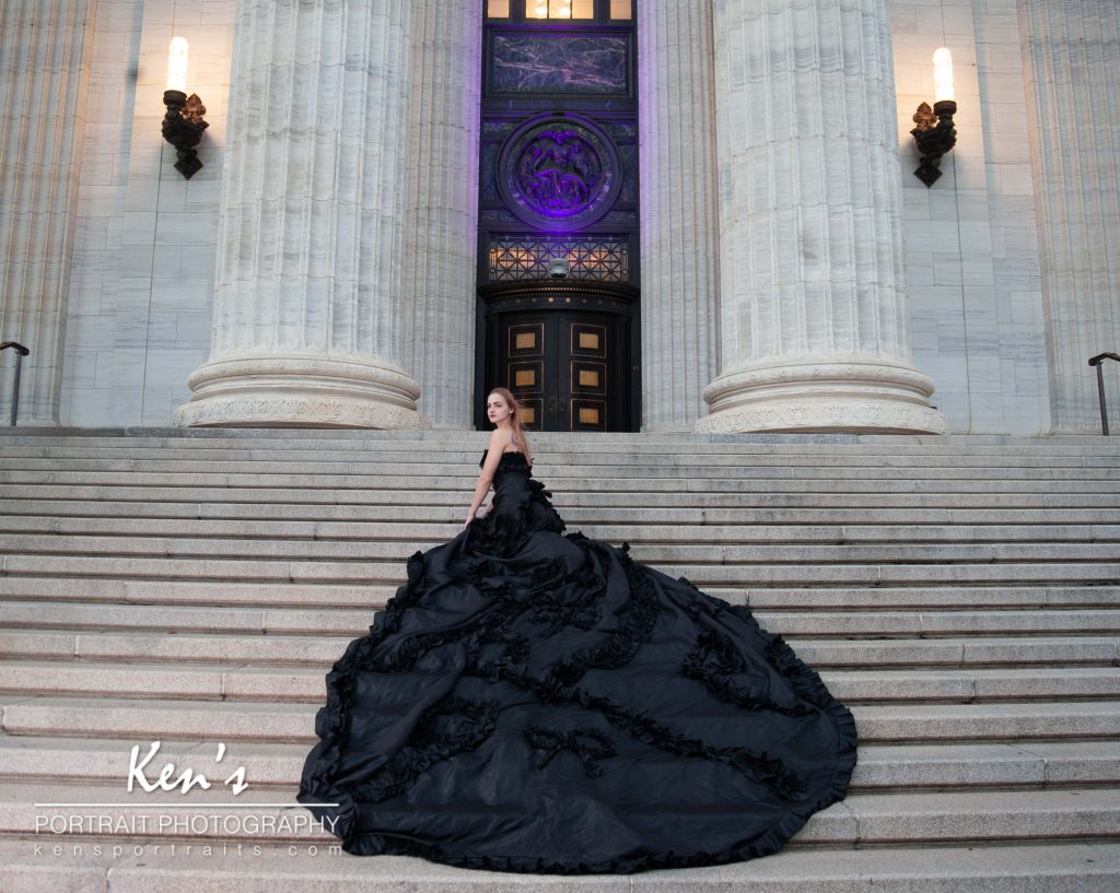 Fantasy Fashion Shoot Part 3 by Kens Portrait Photography. Sara stands on the expansive staircase of the New York State Education Department Building flanked by two of its colossal columns. In this image, the New Your State Education Building is bathed in purple lighting honoring Domestic Violence Awareness Month. Sara is wearing the Bow Tie Noir Gown which is a fantasy fashion gown used by professional photographers for specialized fashion images. The gown is a strapless, straight across neckline, A-line style dress with ruffles and bow ties lining the torso, ruffles and bow patterns flow down the length of the skirt and spill onto the monarch length train. The train is over thirteen feet in length.