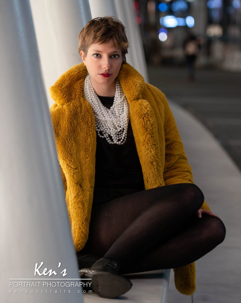 Pearls are Always Appropriate by Kens Portrait Photography. It was Jackie Kennedy Onassis who said ''Pearls are always appropriate''. When Lenny showed up for the shoot she had strings and strings of pearls in her purse. The pearls, with the black dress, and golden faux fur contrast wonderfully with the white starkness of the Oculus. As Lenny sits on a bench outside the Oculus, the light from the shops inside gently light her face.  You can see more of Lenny in New York City Lights and Style as she poses in front of One World Trade Center in New York City sporting a pixie haircut, black leather jacket, and a white hand painted t-shirt. I frequently travel to New York City and have begun to do some on-location street fashion portraits around the town.  The studio for Ken's Portrait Photography is located right on the southwest corner of West Capital Park in Albany, NY. In addition to what can be created in the studio, this historic and architecturally rich area provides beautiful backdrops for professional portraits, couple portraits, senior portraits, family portraits, engagement portraits, and wedding portraits.
