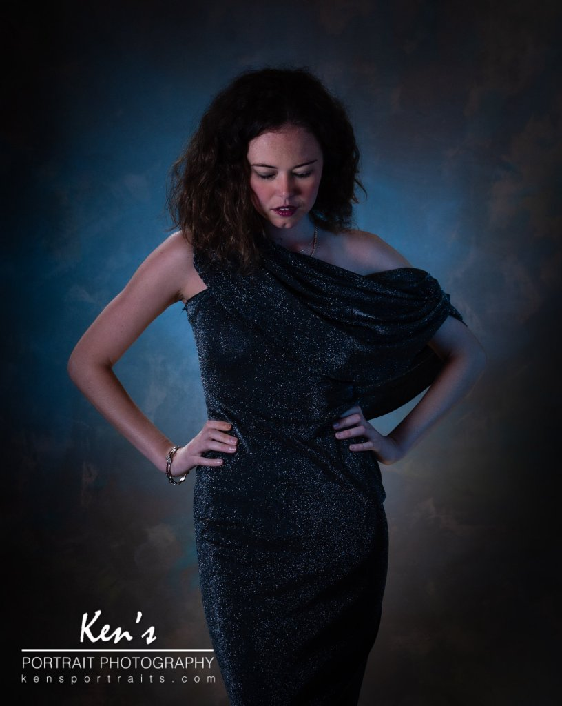 Cool Elegance by Kens Portrait Photography. You have to wonder what Chandra is thinking as she elegantly poses is this beautiful black sequined dress. Blue light bathes the backdrop behind her giving this fashion portrait a cooler lighting effect.  The Fashion Portrait Experience at Ken's Portrait Photography includes an initial consultation, two hours of in studio or on-location photography, a personalized image review session. You can fulfill your fashion dreams by adding professional hair and makeup artistry to the fashion portrait experience.  The studio for Ken's Portrait Photography is located right on the southwest corner of West Capital Park in Albany, NY. In addition to what can be created in the studio, this historic and architecturally rich area provides beautiful backdrops for professional portraits, couple portraits, senior portraits, family portraits, engagement portraits, and wedding portraits.