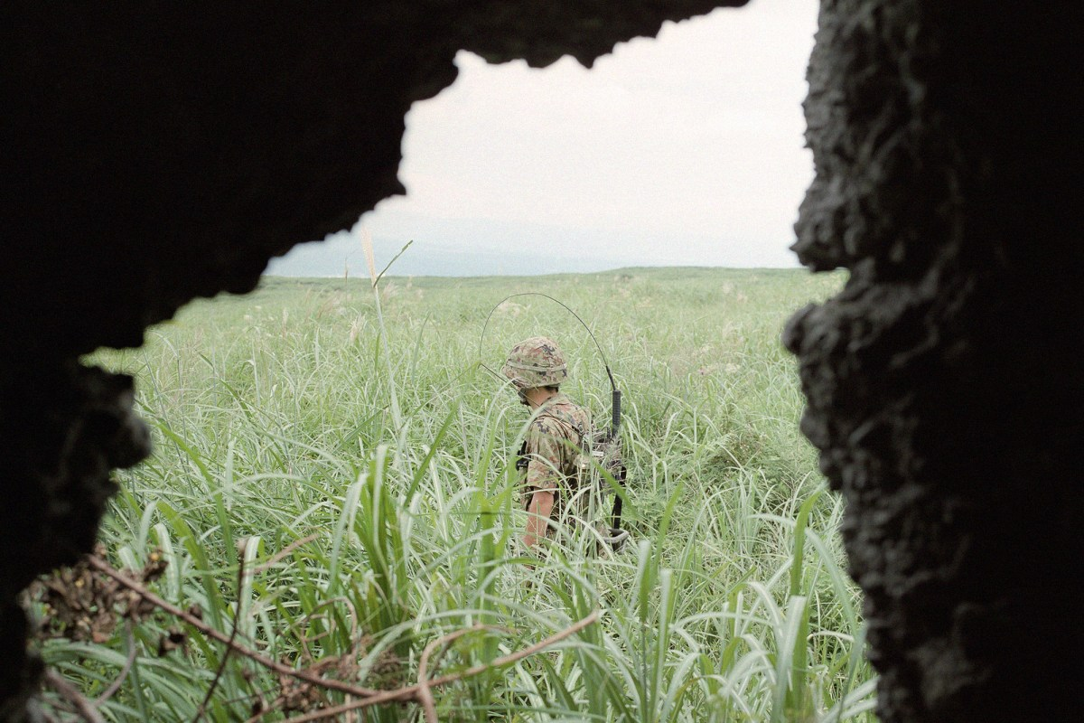 A Japanese Self Defense Force soldier walking around a field during drills. Gotemba, Shizuoka, August 2015.