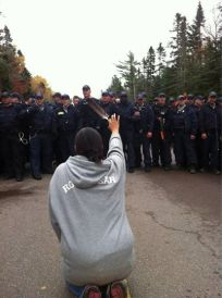 woman on knees in front of police