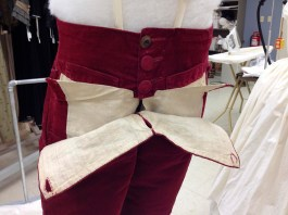This photograph shows the way that the breeches open. The bib-like front flap secures to the front with buttons at each side and at the center front. The buttonhole in the center is formed right in the center front seam.