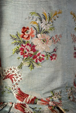 Detail of brocaded textile on bodice showing texture of brocaded silk.