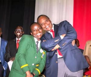 President Uhuru Kenyatta posing for a photo with a High school girl
