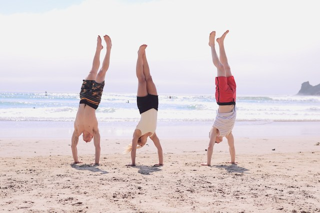 Three peopled doing handstands on the beach
