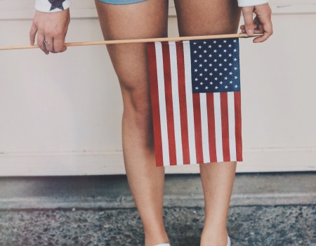 Girl in star shirt, blue shorts, white shoes holding an American Flag