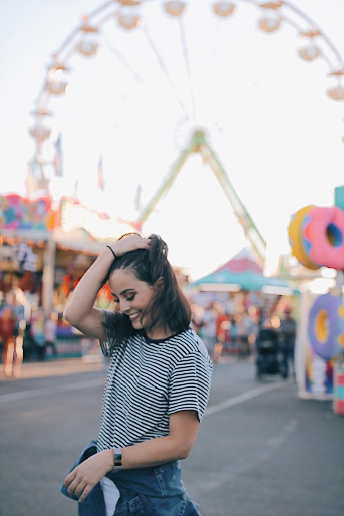 Girl Smiling at the state fair. Ferris wheel in the background.