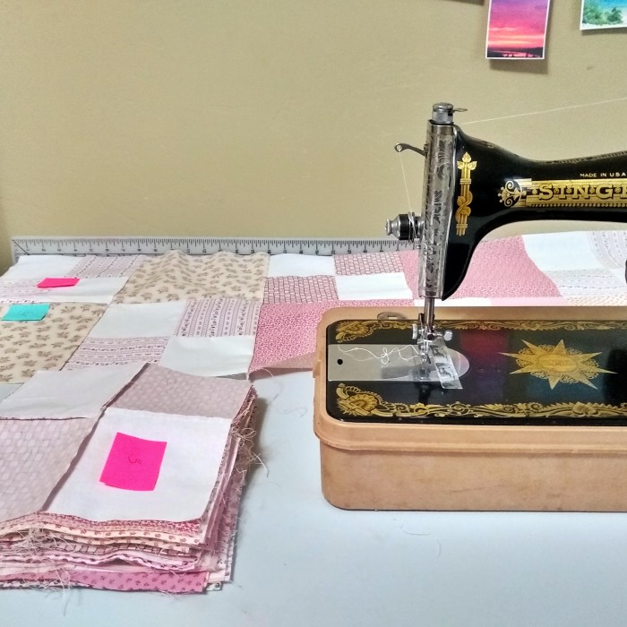 A sewing machine and stacks of patchwork quilt squares with post-it notes on top of each stack