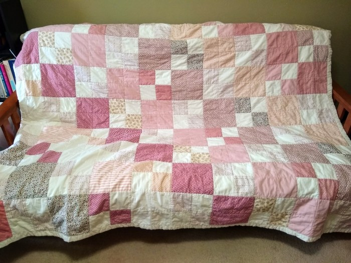 A patchwork quilt in white and shades of pink draped over a couch
