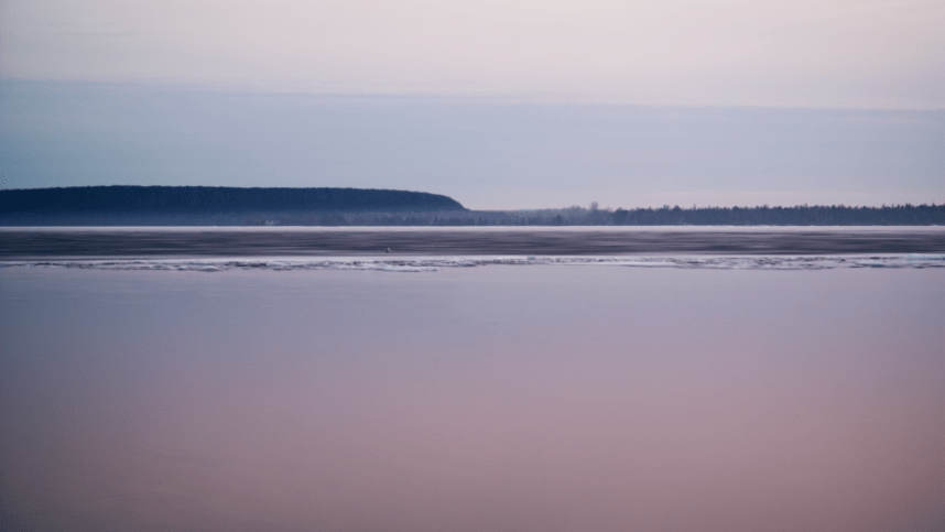 A photo of ice-covered water and the land beyond it in gloomy shades of pink, blue, and gray