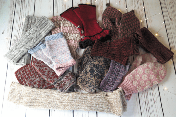 A small pile of hand-knit mittens and fingerless mitts.
