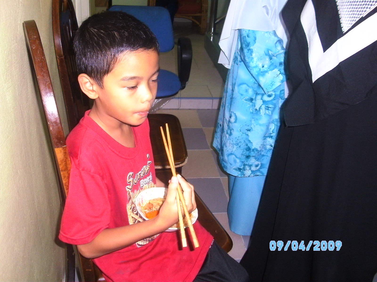 Azzam makan mihun tomyam dengan chopstick.