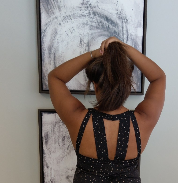 Keri Elaine BCBG Back details on black jumpsuit modern wall art and a ponytail
