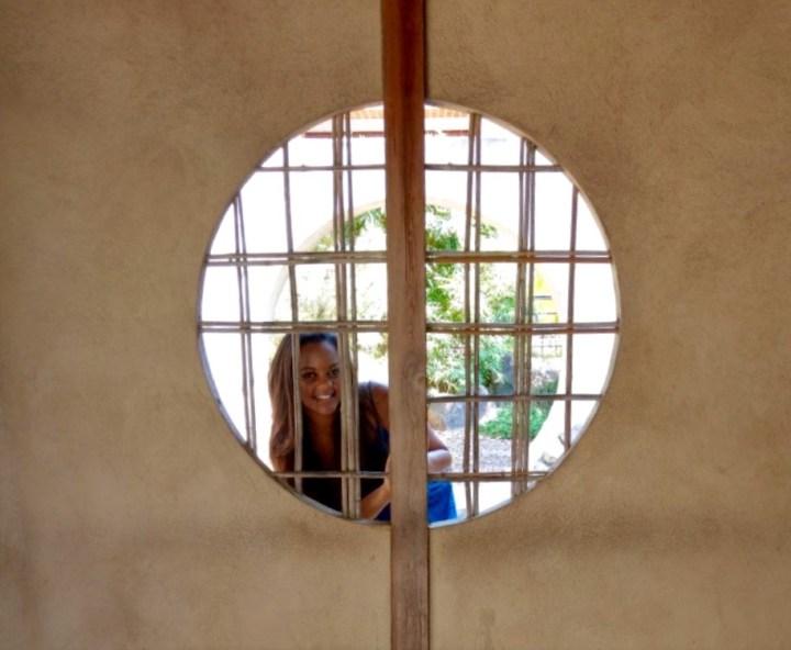 Girl looking through Asian inspired zen garden art. Circular windows and a beautiful woman