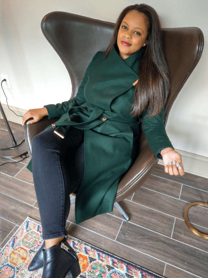 Midcentury modern chair, black girl magic, in a Ted Baker emerald green coat, black ankle booties.