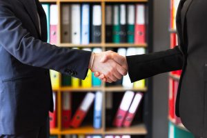 An attorney and his client handshake after a successful business litigation case in Madison.