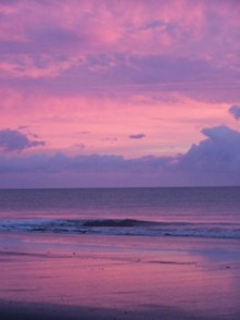 A pink and purple sunset reflected in the waves of Playa Zancudo, Costa Rica in the Puntarenas Province of the South Pacific Coast across from the Osa Peninsula.