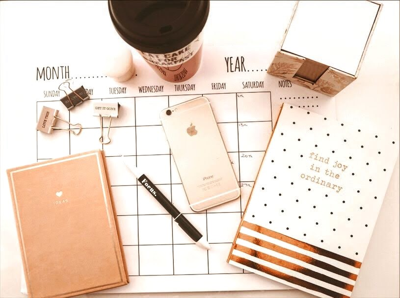 a desk planner, notebook, phone and pen all sit on a desk