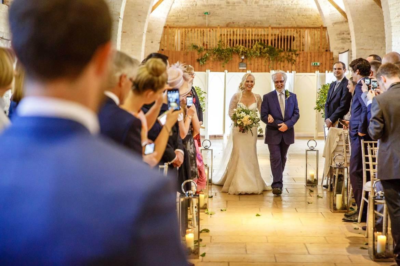 Bride walks down the aisle at Tithe Barn wedding