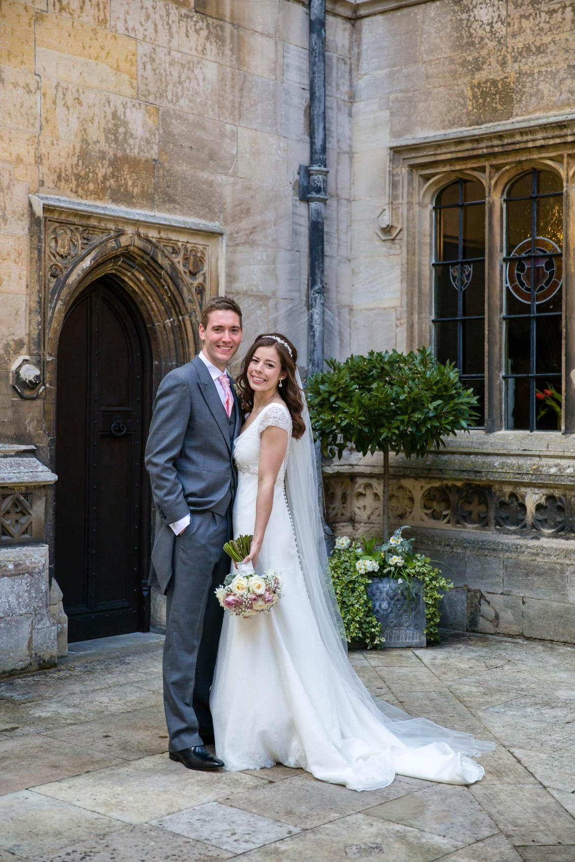 A full length portrait of Amy and Jack in the courtyard of Hengrave Hall.