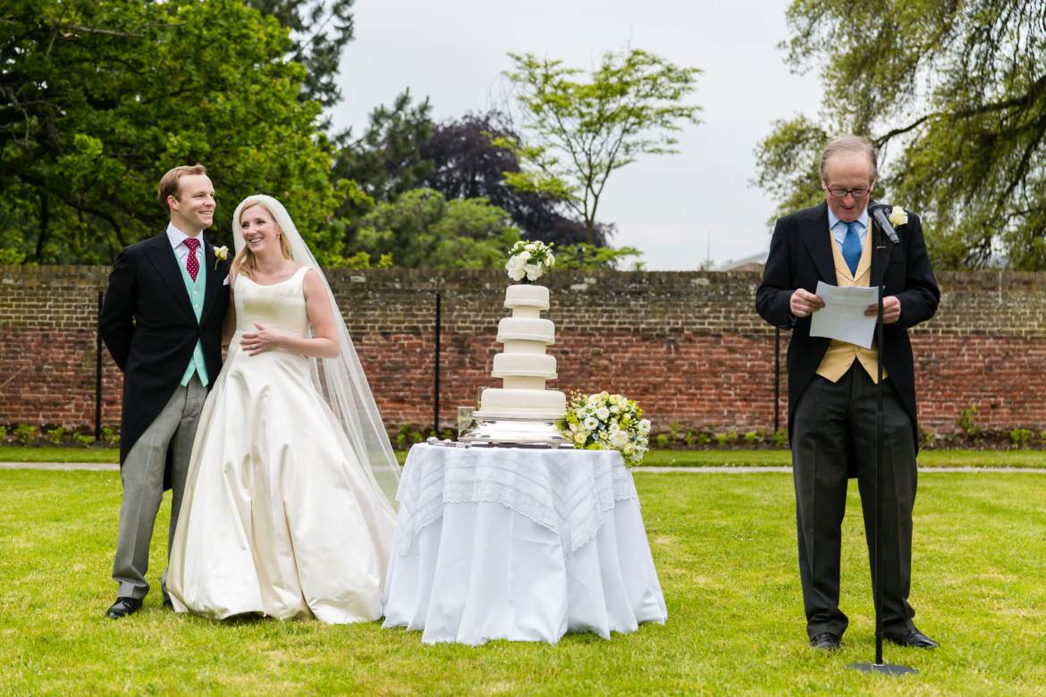 The bride and groom stand next to their wedding cake and listen to the speech