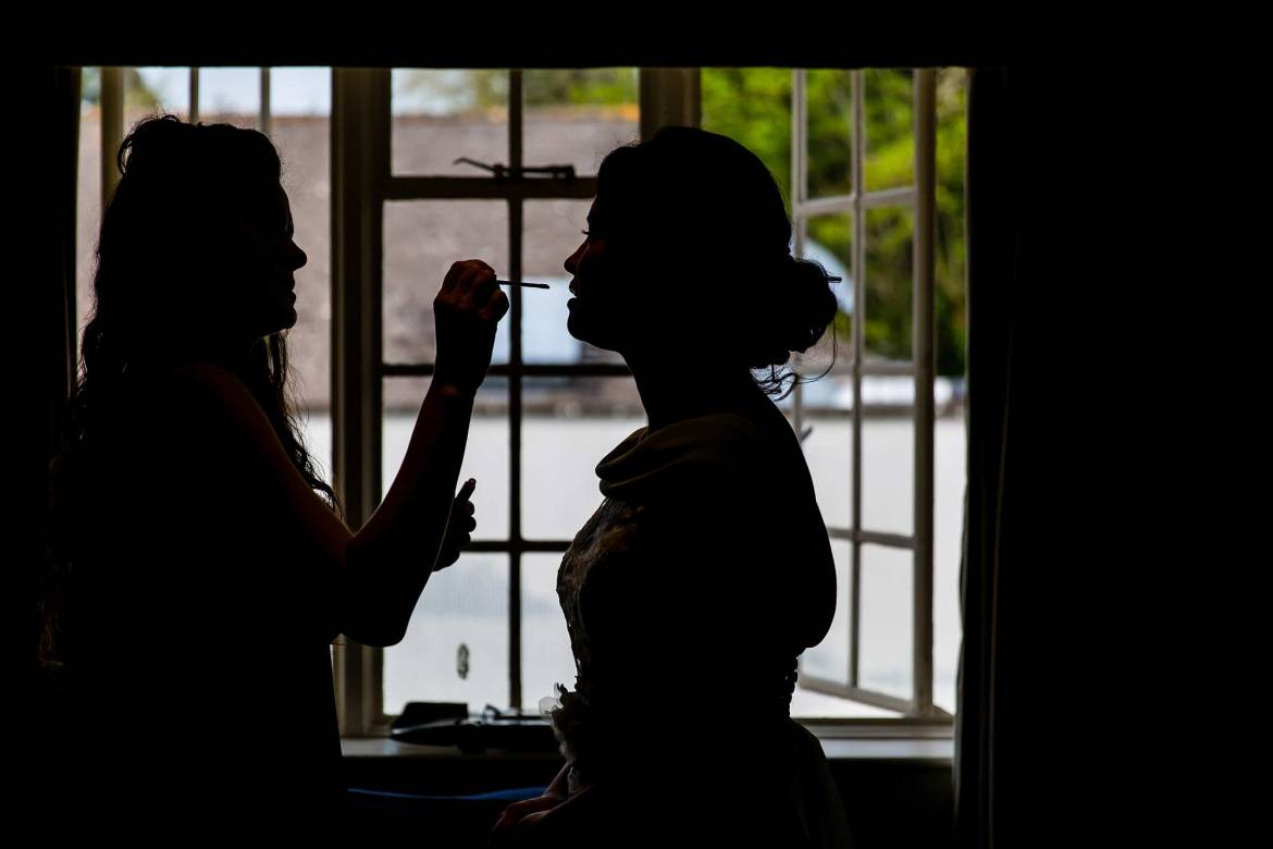 silhouette on rachel having her lipstick applied by her make up artist