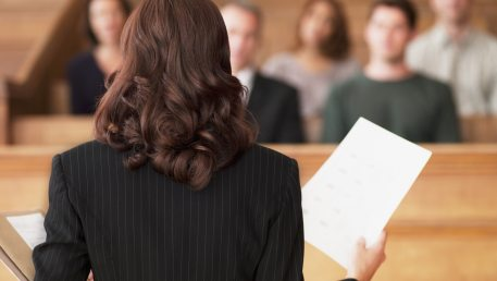Criminal lawyer standing in front of jury arguing client's defense