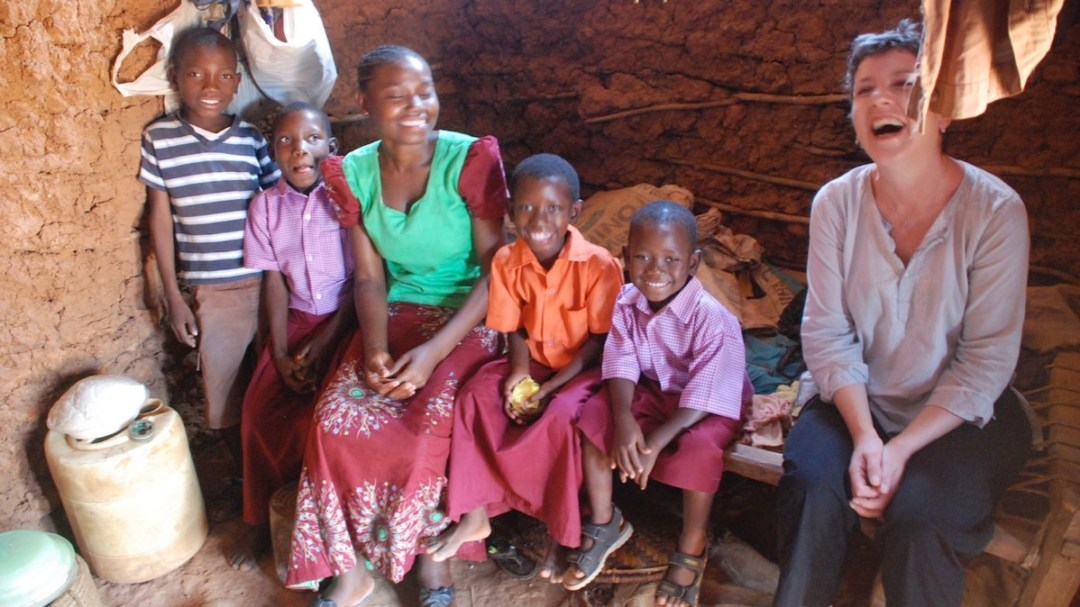 A family and Kate Nokes sitting on a bed in a traditional house in Kilifi County