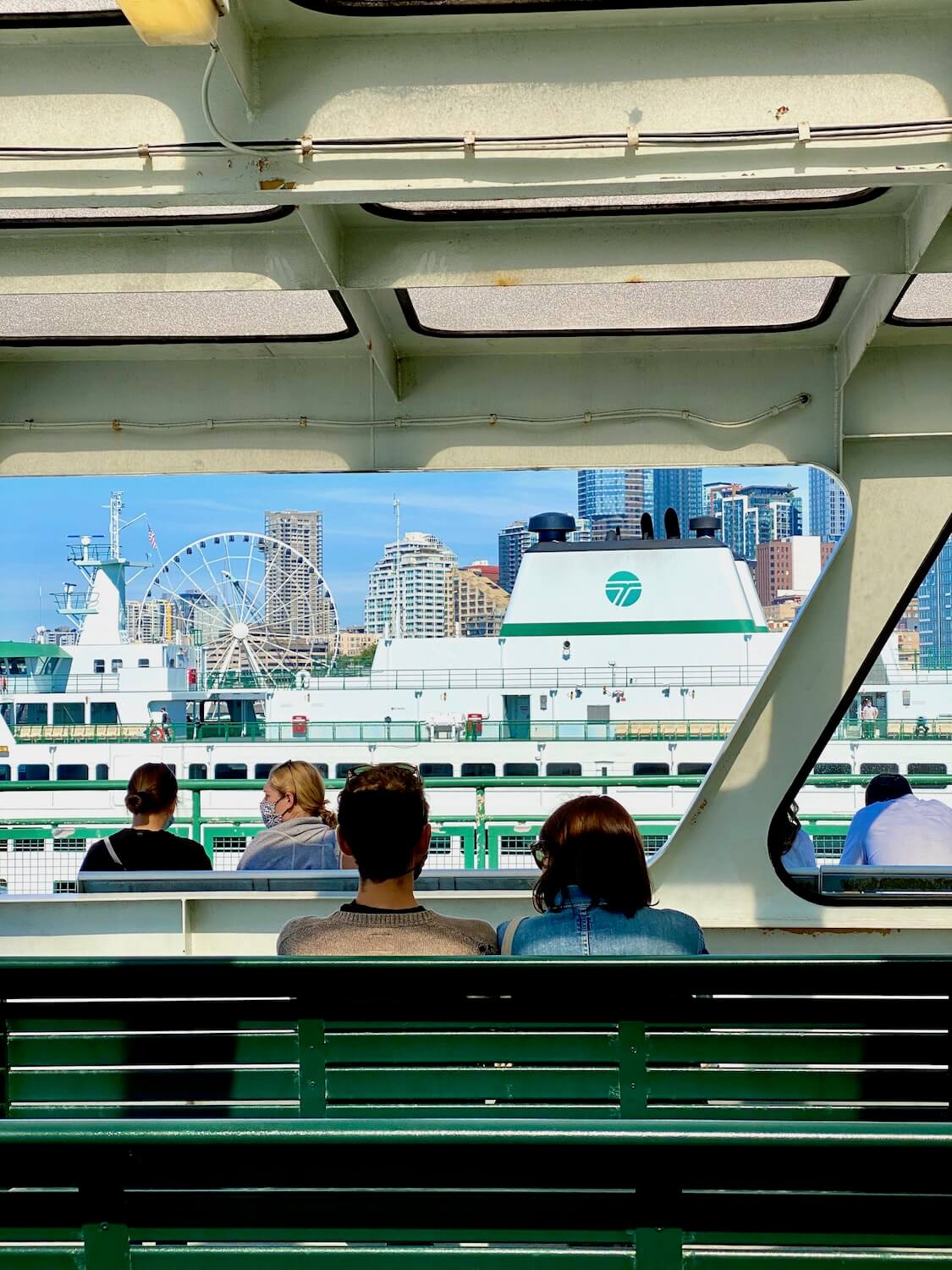No travel to the Pacific Northwest is complete without a ride across the Salish Sea. Here ferry passengers look out toward Downtown Seattle as the ferry prepares to navigate it's way to a destination on the other side of the Puget Sound. The benches are painted green and another ferry is in the background, just in front of Seattle's Big Wheel attraction downtown.