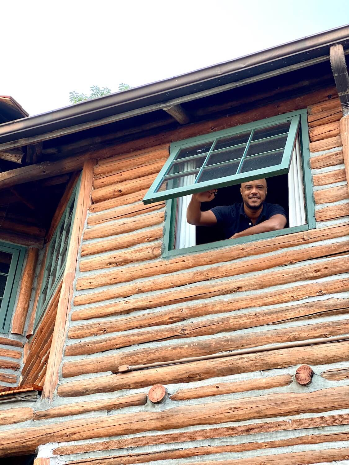 A man looks out a window with nine panes and green trim. The room is on the second floor of the main building of Captain Whidbey inn. The walls of the loge are a series of logs patched together with cement.