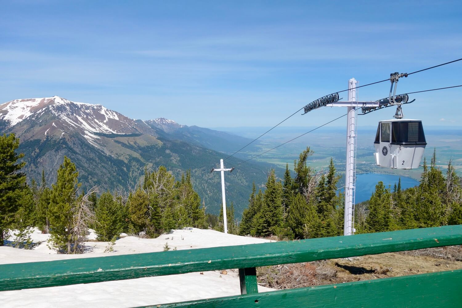 The Wallowa Lake Tramway ascends 3600 feet in about fifteen minutes, and this photo is taken from the green railing of the Summit Pub at the top of the mountain. Crescent shaped Wallowa Lake is in the background as well as the town of Joseph, Oregon. A gondola makes its way to the final summit.