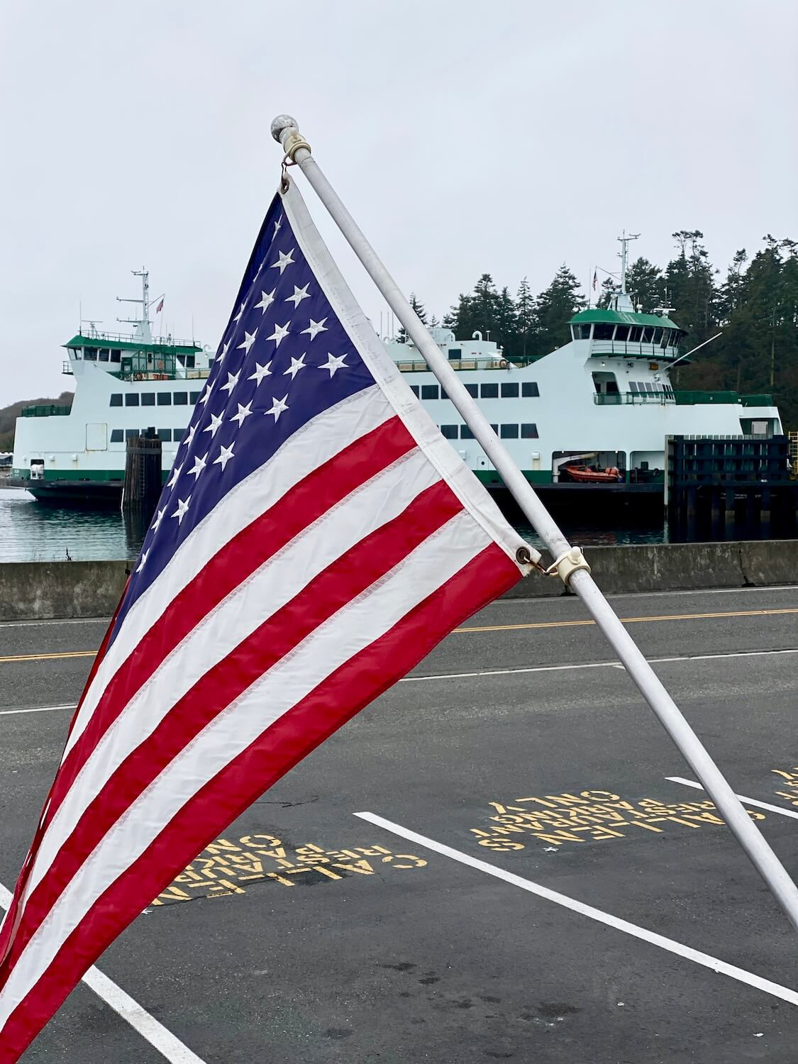 An American flag flies in front of a restaurant while a Washington State Ferry pulls into the dock at Coupeville. The ferry is painted white with green trim.