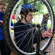 Mies vaihtaa polkupyörän rengasta.