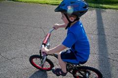 Lapsi ajaa pyörällä.