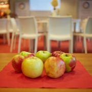 Omenoita pöydällä, taustalla pöytäryhmiä.