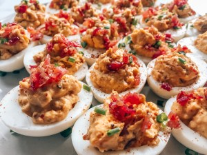 Deviled eggs on a plate with bacon and chives