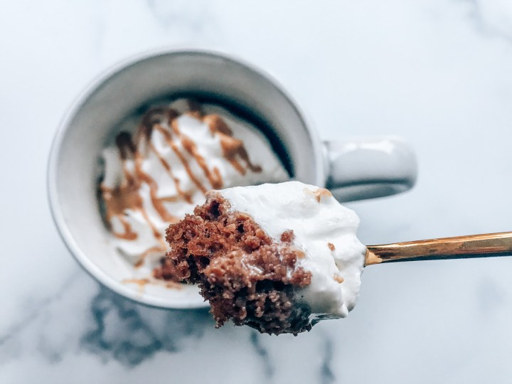 Chocolate cake in a mug with peanut butter and whipped cream.