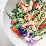 Bowl of arugula, chicken, almonds, cheese, apples, and edible flowers