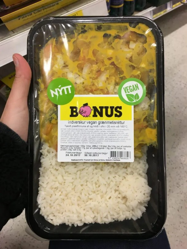 A hand holding a prepared food package from Bonus food store, with a large circular vegan sticker featured next to the food label.