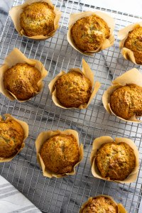 Overhead shot of banana coconut muffins, arranged on a metal baking sheet over marble