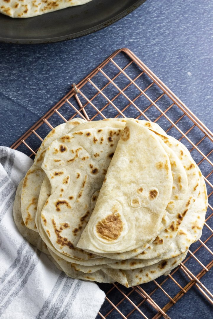 A pile of soft, sourdough flour tortillas shot overhead on a blue background with a soft grey and white striped towel.