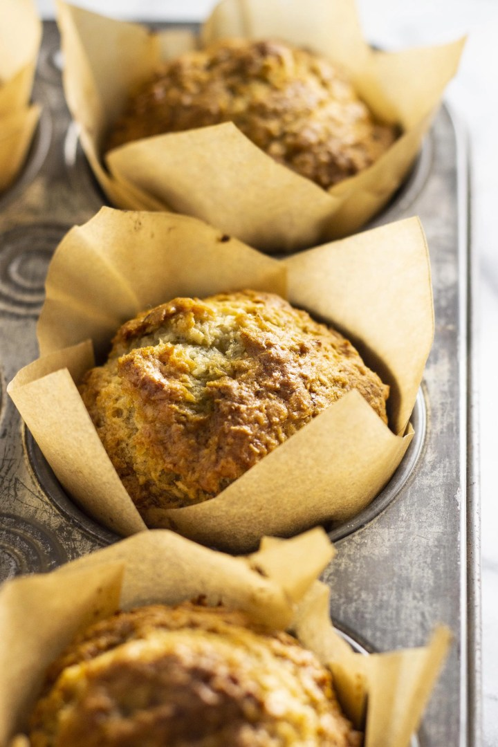 banana coconut muffins- one muffin close up, in a tray