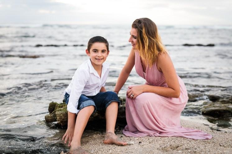 Mère et fils assis sur le sable de la plage de Saint-Leu