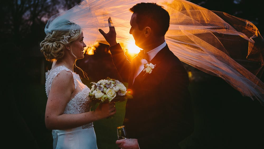 At sunset the groom holds the bride's veil as it blows in the wind